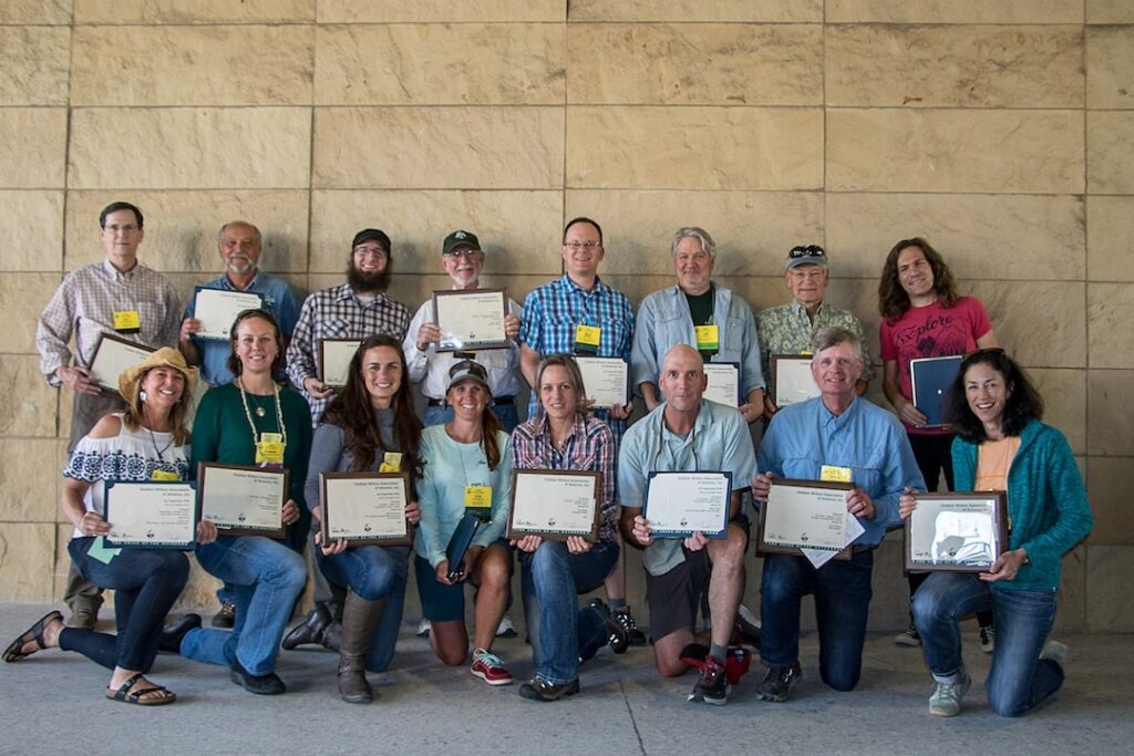 Two rows of winners of the OWAA Excellence in Craft award pose with plaques
