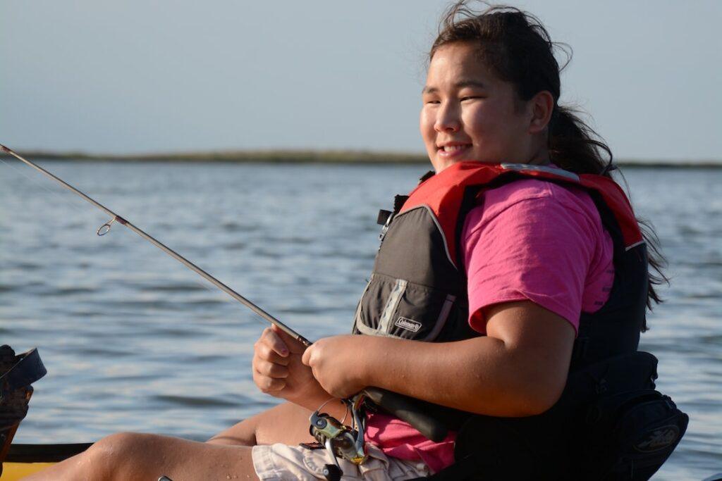 A young girl fishes from an inflatable raft