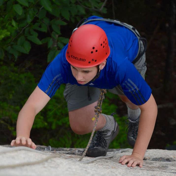 A yonug person climbs a rock face