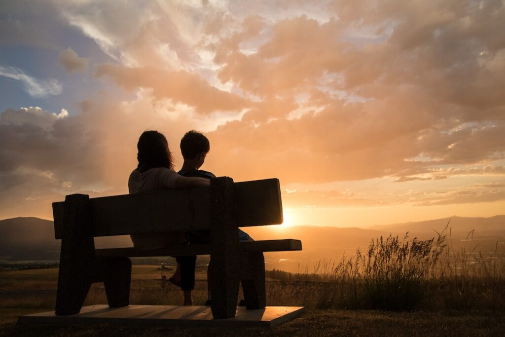 Two people on a bench look out at the sunset