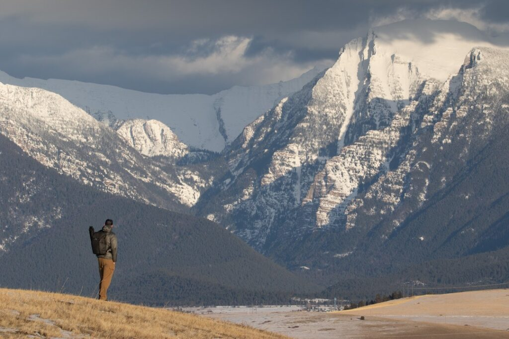An OWAA member stands gazing at the mountains