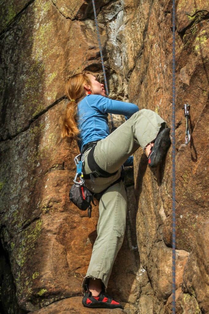 A woman scales a sheer rock wall