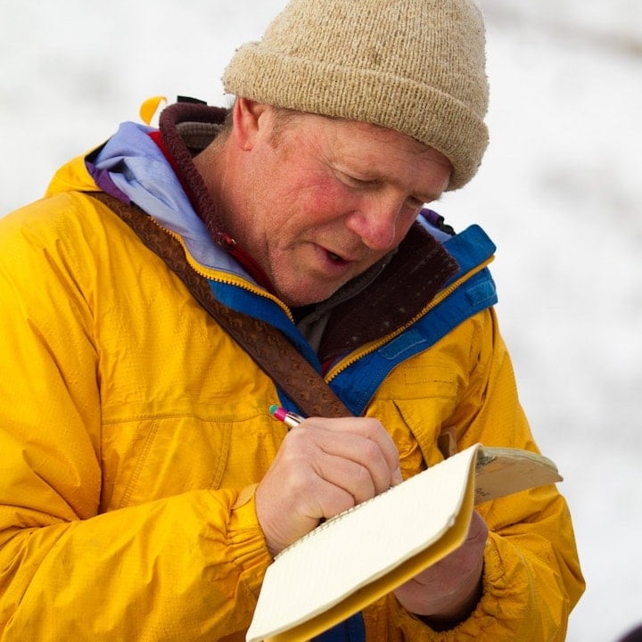 An OWAA member in cold weather gear writes in a notebook