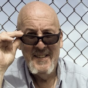 Headshot of Steve Griffin lowering his sunglasses with a chainlink fence background