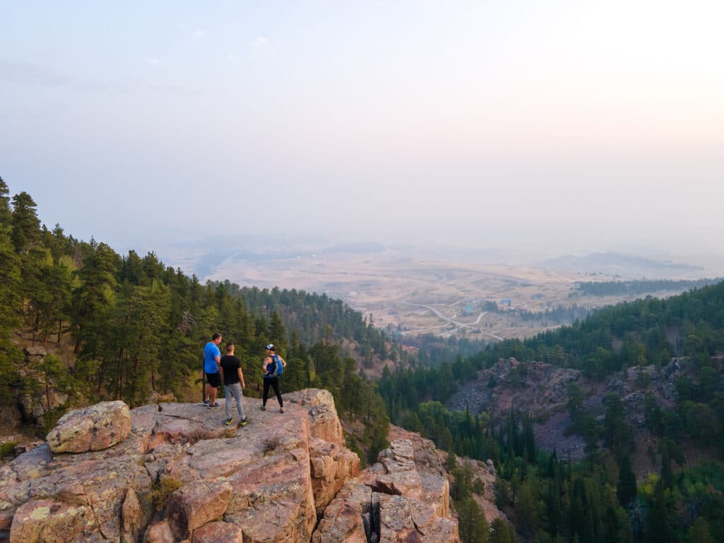 Three hikers stand on the edge of a rock ledge looking out over a vast wooded landscape