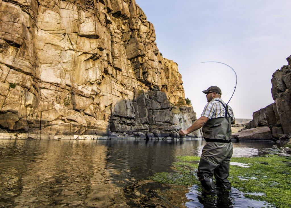 A man fly fishes in a rocky canyon