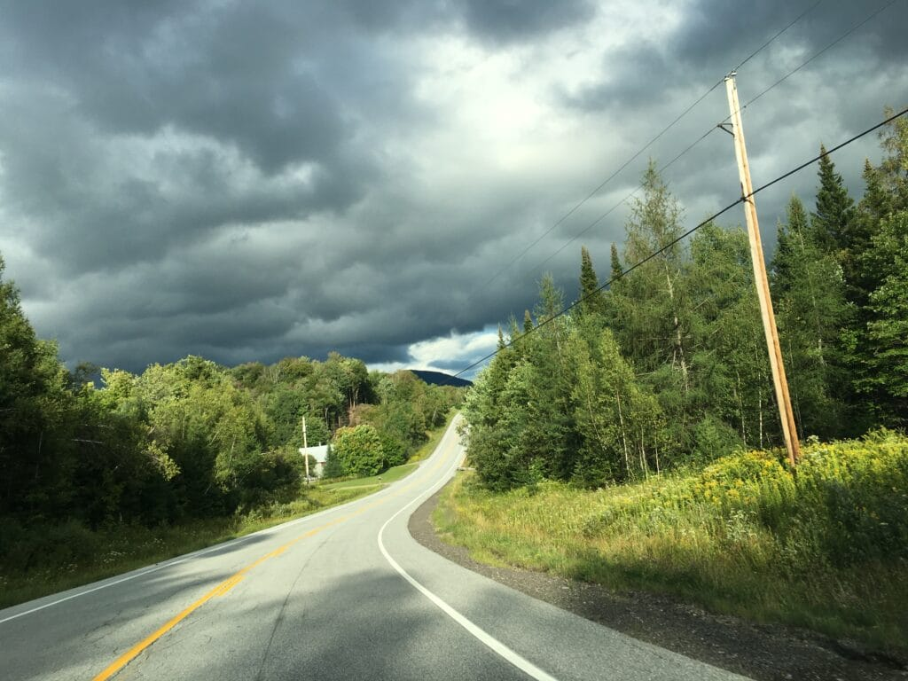 A curving stretch of road in Vermont, with verdant trees on either side and overcast skies