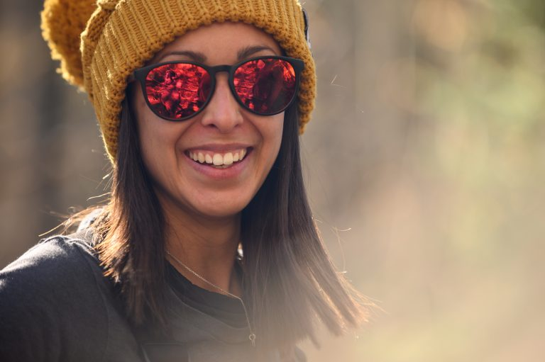 A woman in sunglasses smiles for the camera