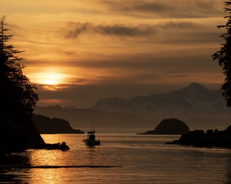 The sun sets near Mount Tanaku, silhouetting a small boat