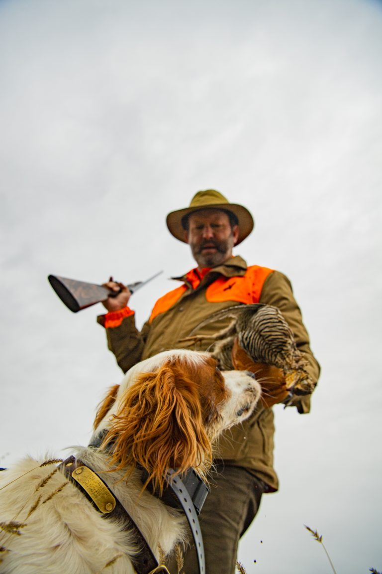 A hunter stands with a dog
