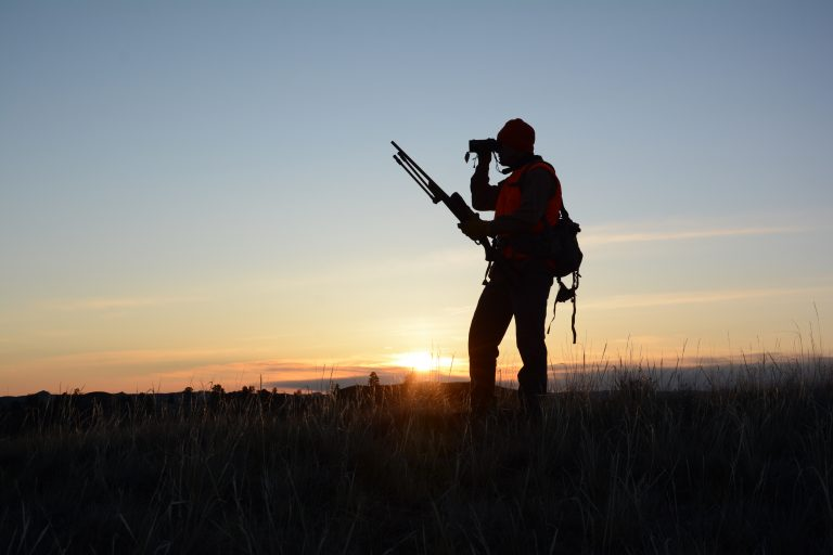 A hunter silhouetted against the horizon