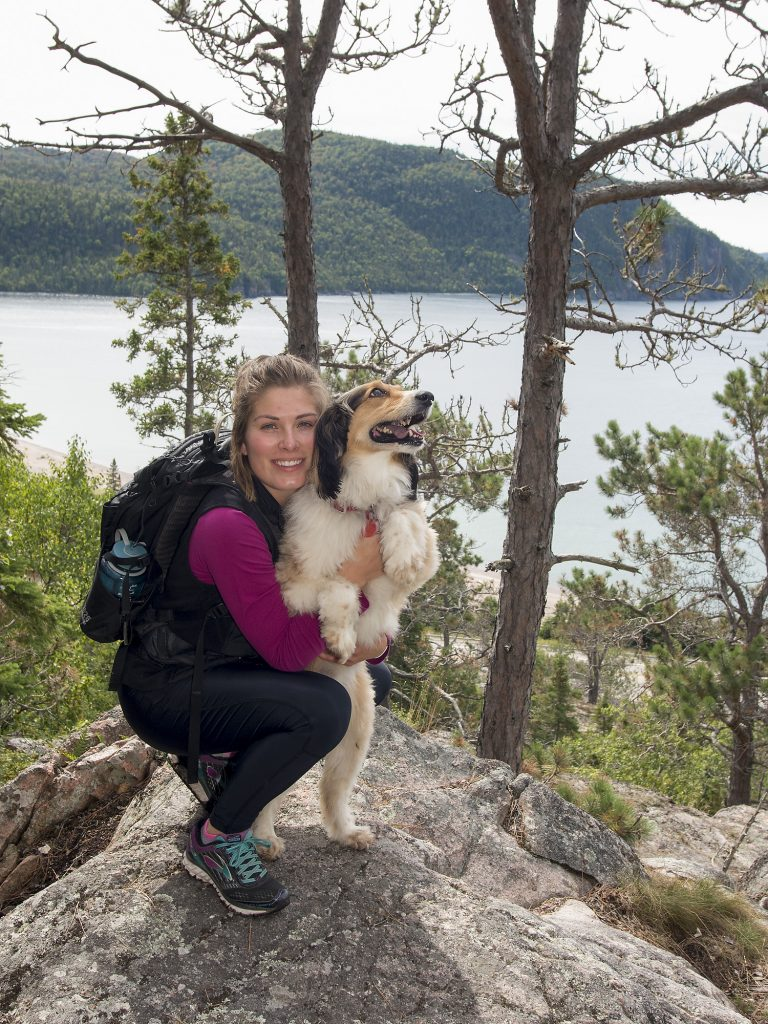 A hiker hugs her dog in front of a lake